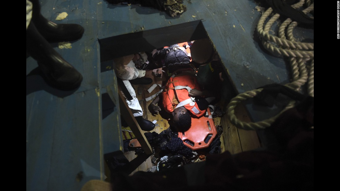 Members of Proactiva Open Arms NGO prepare to evacuate a body on a stretcher from the third level of a wooden vessel.