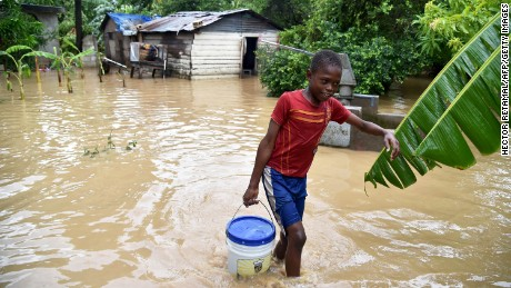 Jonnathan fetches clean water for his mother cleaning his home flooded by the overflowing of the La Rouyonne river in the commune of Leogane, south of Port-au-Prince, October 5, 2016. Haiti and the eastern tip of Cuba -- blasted by Matthew on October 4, 2016 -- began the messy and probably grim task of assessing the storm's toll. Matthew hit them as a Category Four hurricane but has since been downgraded to three, on a scale of five, by the US National Hurricane Center.  / AFP / HECTOR RETAMAL        (Photo credit should read HECTOR RETAMAL/AFP/Getty Images)