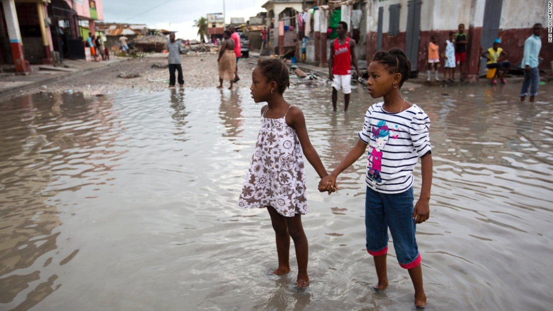 Girls hold hands as they help each other wade through a flooded street in Les Cayes on October 6.