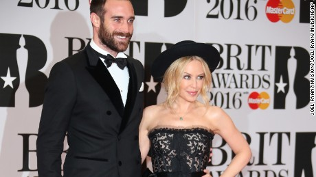 Singer Kylie Minogue, right, and Joshua Sasse pose for photographers upon arrival for the Brit Awards 2016 at the 02 Arena in London, Wednesday, Feb. 24, 2016. (Photo by Joel Ryan/Invision/AP)