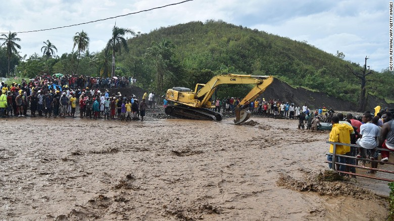Haitians wait to cross the river in Petit Goave where a bridge collapsed cutting off a main route to the devastated south of the country