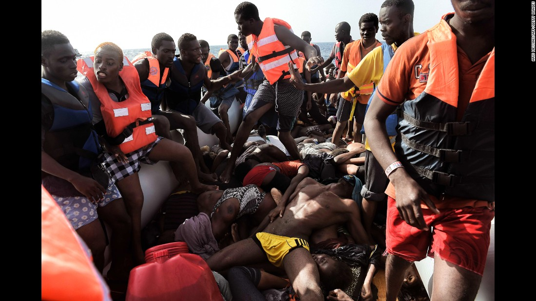 """Migrants step over dead bodies <a href=""""http://www.cnn.com/2016/10/06/europe/migrant-boats-libya-aris-messinis/index.html"""" target=""""_blank"""">while being rescued</a> in the Mediterranean Sea north of Libya on Tuesday, October 4. Photographer Aris Messinis said the rescuers counted 29 dead bodies -- 10 men and 19 women, all between 20 and 30 years old. """"I've (seen) in my career a lot of death,"""" he said. """"I cover war zones, conflict and everything. I see a lot of death and suffering, but this is something different. Completely different."""""""