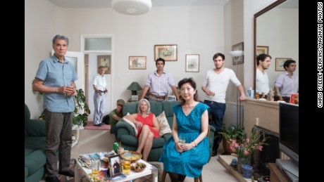 A portrait of photographer Chris Steele-Perkins and his family in London. Steele-Perkins is standing in the doorway.