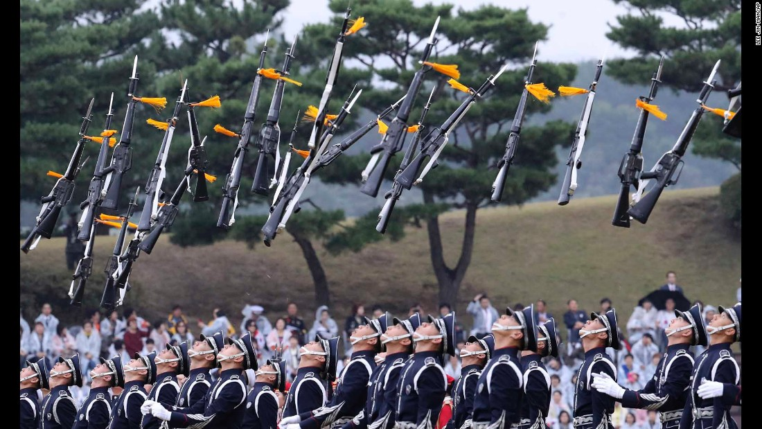 Members of a military honor guard throw their guns into the air during Armed Forces Day celebrations in Gyeryong, South Korea, on Saturday, October 1.
