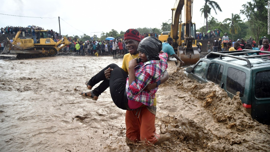 A woman is carried across the river La Digue in Petit Goave where a bridge collapsed during the torrential rains.