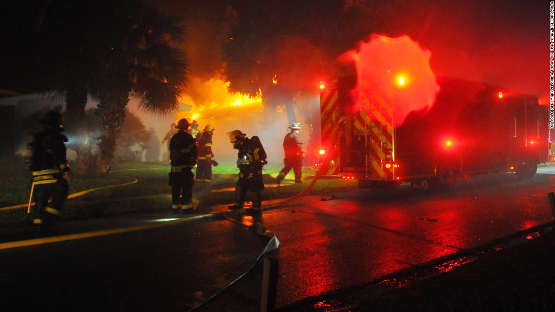 Firefighters respond to a pre-dawn house fire in Satellite Beach, Florida, that was possibly caused by a downed power line on October 7.