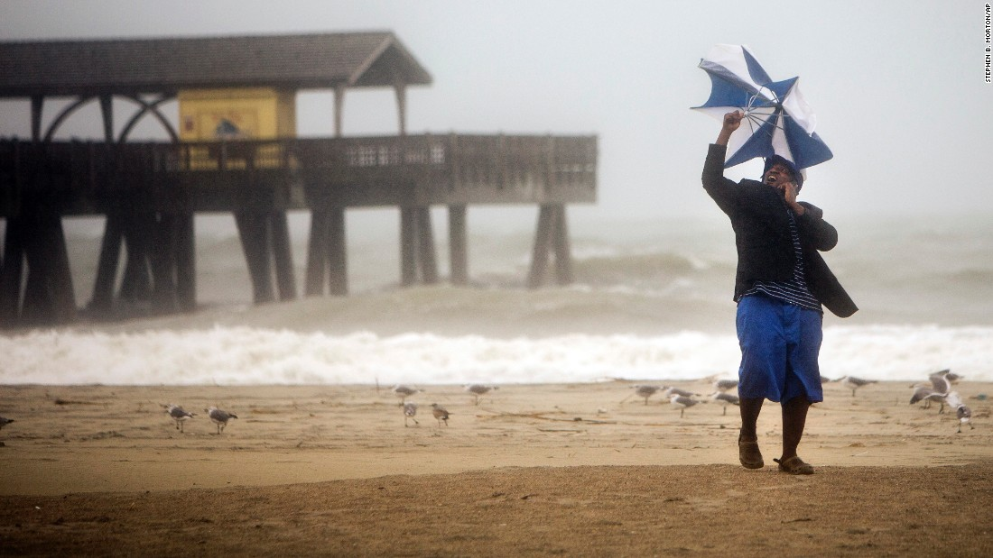 Preston Payne tries to hold his umbrella on Georgia's Tybee Island on October 7.