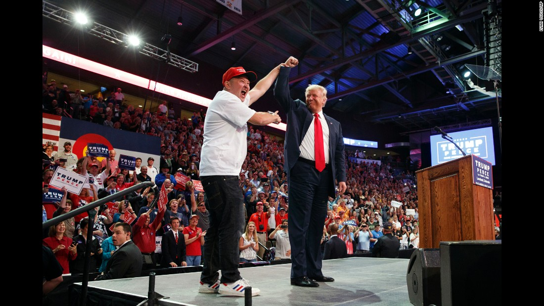 Peter Riehl, of Lone Tree, Colorado, holds up the hand of Republican presidential candidate Donald Trump during a campaign rally in Loveland, Colorado, on Monday, October 3.