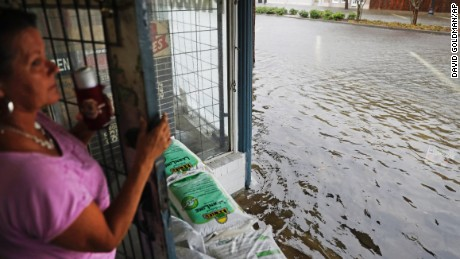 Debbie Tait, stands behind sand bags in the entrance to her hardware store as the street floods with water from Hurricane Matthew in downtown Brunswick, Ga.