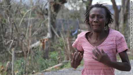 A woman runs in the streets seeking aid in the aftermath of Hurricane Matthew in Haiti.