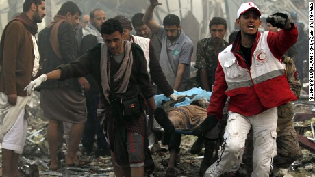 """Yemeni rescue workers carry a victim on a stretcher amid the rubble of a destroyed building following reported airstrikes by Saudi-led coalition air-planes on the capital Sanaa on October 8, 2016.Rebels in control of Yemen's capital accused the Saudi-led coalition fighting them of killing or wounding dozens of people in air strikes on Sanaa. The insurgent-controlled news site sabanews.net said that coalition planes hit a building in the capital where people had gathered to mourn the death of an official, resulting in """"dozens of dead or wounded"""". / AFP / MOHAMMED HUWAIS        (Photo credit should read MOHAMMED HUWAIS/AFP/Getty Images)"""
