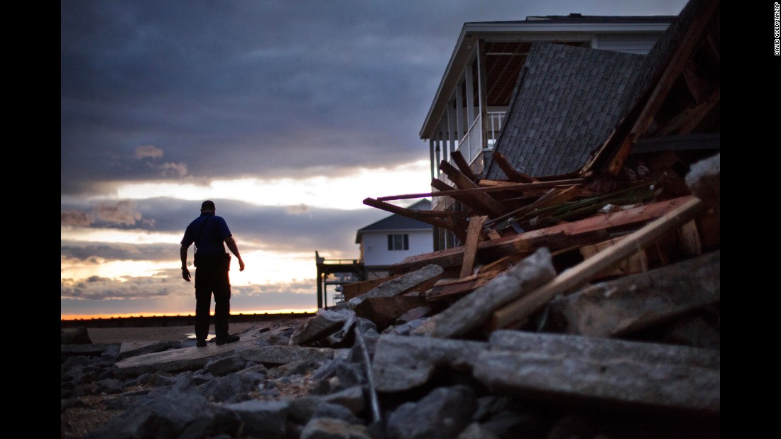 officer steps through the remnants of a home leveled by Hurricane ...