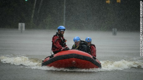 A water rescue team heads to shore at the onramp of MLK Freeway after rescuing Derrick Williams from the flood waters on Robeson Street on Saturday, Oct. 8, 2016, in Fayetteville, N.C.  A fast-weakening Hurricane Matthew continued its march along the Atlantic coast Saturday, lashing two of the South's most historic cities and some of its most popular resort islands, flattening trees, swamping streets and knocking out power to hundreds of thousands.  (Andrew Craft /The Fayetteville Observer via AP)