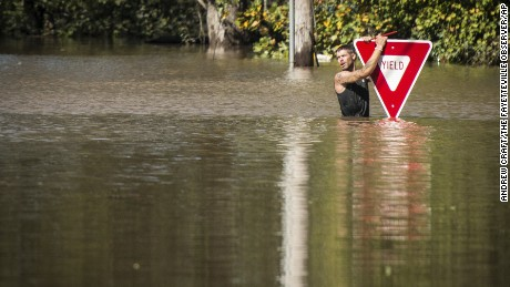 A man holds onto a sign after trying to swim out to help a stranded truck driver in Hope Mills, North Carolina, on Sunday.