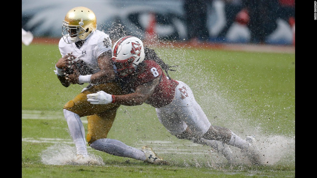 North Carolina State defensive back Dravious Wright tackles Notre Dame wide receiver C.J. Sanders during a college football game in Raleigh, North Carolina, on Saturday, October 8. The game was played in a torrential downpour caused by Hurricane Matthew.