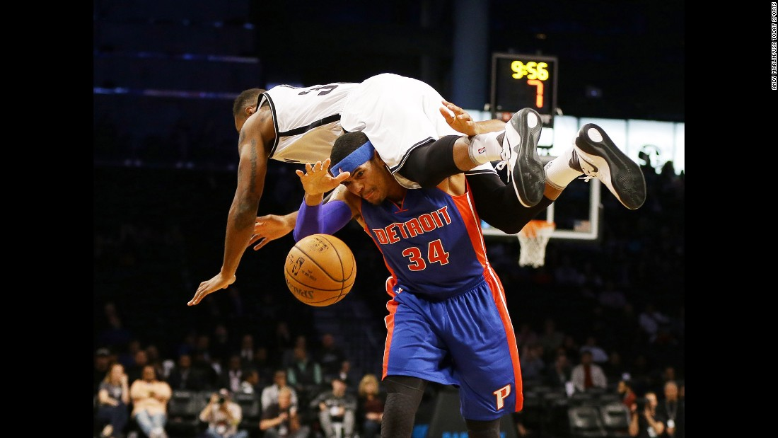 Brooklyn's Trevor Booker falls over Detroit's Tobias Harris after trying to block his shot during an NBA preseason game on Thursday, October 6.