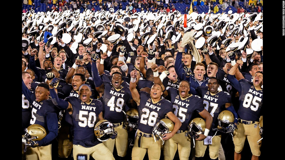 Navy players celebrate with midshipmen after upsetting Houston 46-40 on Saturday, October 8.