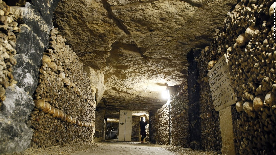 """At the end of the eighteenth century Paris had a problem: its cemeteries were full. In a bid to prevent overcrowding, authorities dove beneath terra firma, converting quarries which built the city into catacombs. These underground passages, walled with bone, house the remains of generations of Parisians, including victims of the guillotine and some of its most famous names. It is estimated there are<a href=""""http://www.catacombes.paris.fr/en/catacombs/more-2000-years-history"""" target=""""_blank""""> six to seven million</a> held within the catacombs. Five stories down and constantly 57 degrees, a tour of the spooky site covers 1.2 miles of passageways."""