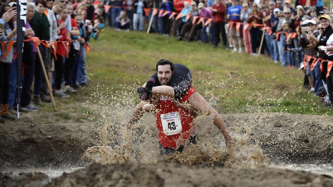 Elliot Storey carries his wife, Giana, through a mud pit as they compete in the North American Wife Carrying Championship on Saturday, October 8. The Storeys defeated 43 other couples to win the obstacle race in Newry, Maine.