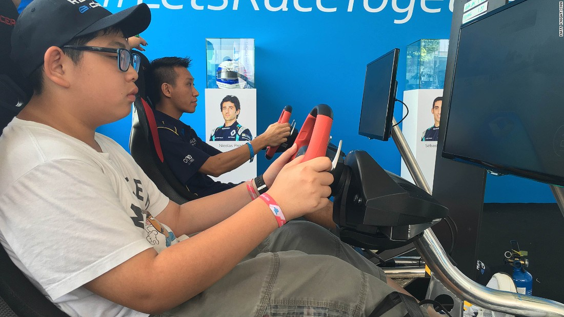 Fans trying their hand a driving game in the Renault e.dams stand.