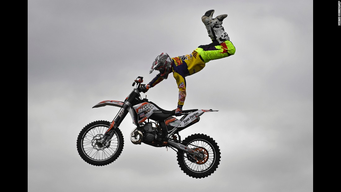 A stunt driver shows off his skills at a motorcycle exhibition in Cologne, Germany, on Friday, October 7.