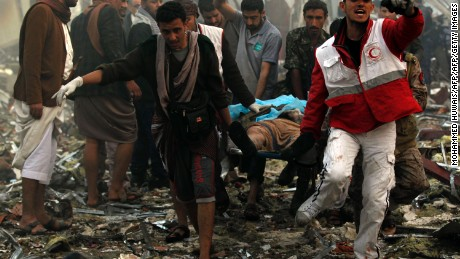 """Yemeni rescue workers carry a victim on a stretcher amid the rubble of a destroyed funeral hall building following reported airstrikes by Saudi-led coalition air-planes on the capital Sanaa on October 8, 2016. Rebels in control of Yemen's capital accused the Saudi-led coalition fighting them of killing or wounding dozens of people in air strikes on Sanaa. The insurgent-controlled news site sabanews.net said that coalition planes hit a building in the capital where people had gathered to mourn the death of an official, resulting in """"dozens of dead or wounded"""". / AFP / MOHAMMED HUWAIS        (Photo credit should read MOHAMMED HUWAIS/AFP/Getty Images)"""