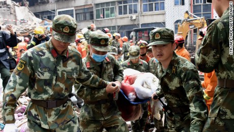 Rescuers carry an injured survivor on a stretcher at an accident site after  in Wenzhou, in China's Zhejiang province on October 10.