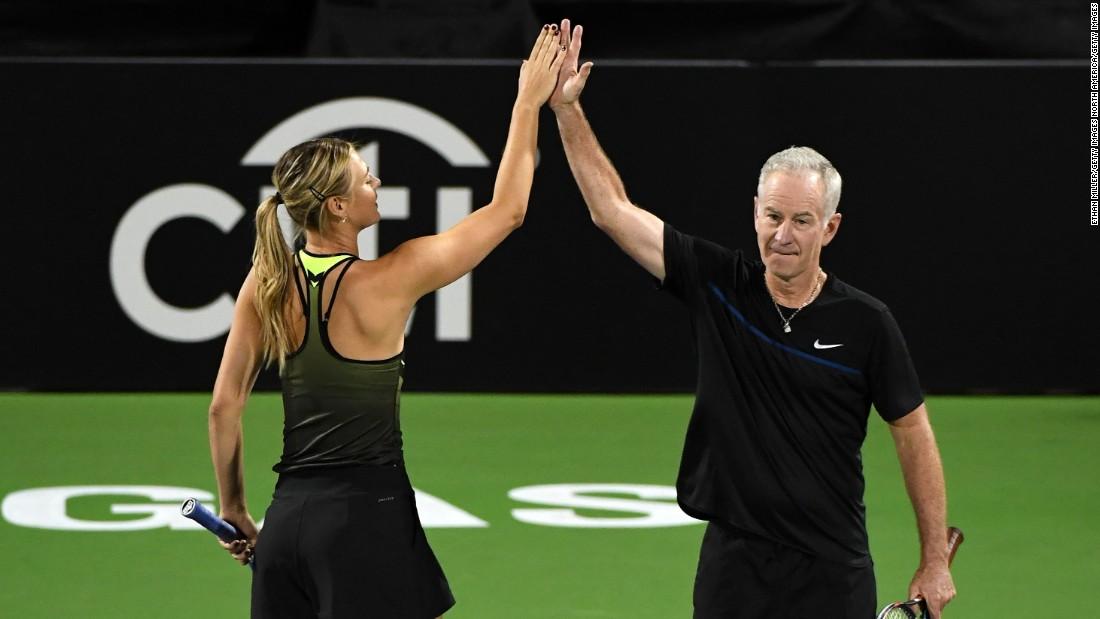 Sharapova celebrates winning a point with partner McEnroe when they teamed up against Roddick and Navratilova.