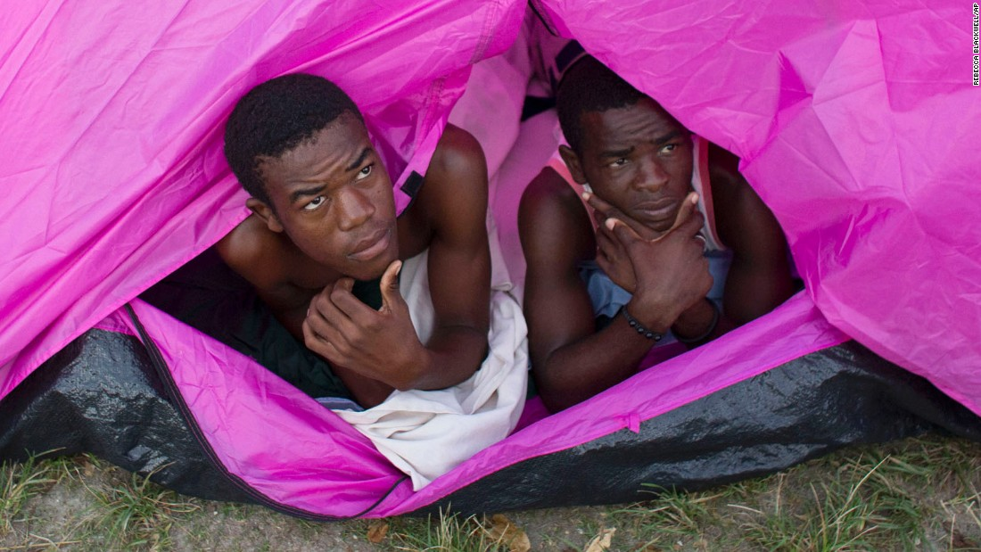 Two young men who lost their homes awake from a tent in the courtyard of a school where they took shelter in Port Salut on October 10.