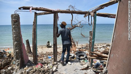 """TOPSHOT - A man stands next to a destroyed house in Les Cayes, Haiti on October 10, 2016, following the passage of Hurricane Matthew.  Haiti faces a humanitarian crisis that requires a """"massive response"""" from the international community, the United Nations chief said , with at least 1.4 million people needing emergency aid following last week's battering by Hurricane Matthew. / AFP / HECTOR RETAMAL        (Photo credit should read HECTOR RETAMAL/AFP/Getty Images)"""