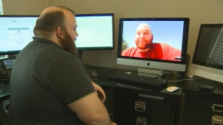 Craig Williams, left, talks with his brother Chris Williams, on monitor.