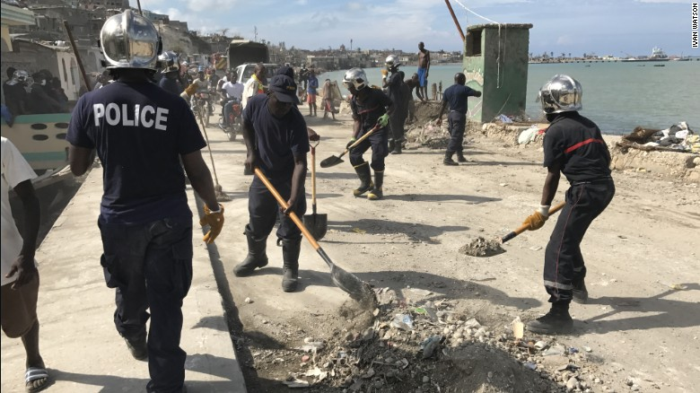 Local police work alongside volunteers cleaning up debris left by Hurricane Matthew along the waterfront in the town of Jeremie.
