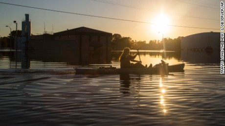 Buckley Miller paddles a canoe past a flooded water treatment plant  in downtown Lumberton.