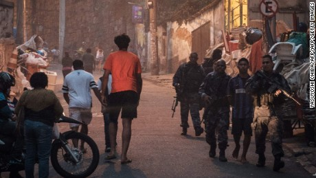 Police officers walk out of the Pavao-Pavaozinho favela with arrested suspects after clashes between drug dealers inside the shantytown  -between Copacabana and Ipanema- in Rio de Janeiro, Brazil, on October 10, 2016.  The Pacifying Police Unit (UPP) was attacked during the gunfights and the commander was injured . / AFP / YASUYOSHI CHIBA        (Photo credit should read YASUYOSHI CHIBA/AFP/Getty Images)