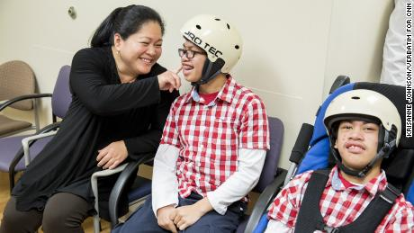 Arlene Aguirre waits with her twin sons Clarence, left, 14, and Carl, right, 14, at Dr. James T. Goodrich's office at The Children's Hospital at Montefiore. Dr. Goodrich separated the conjoined twins in 2004.