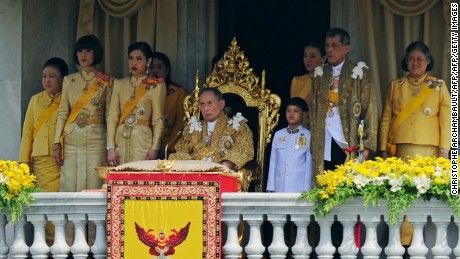 Thai King Bhumibol Adulyadej (C) is surrounded by his daughters Princesses Ubol Ratana (2nd L), Chulabhorn (3rd L), Sirindhorn (R), his son Prince Maha Vajiralongkorn (2nd R) and his grand-son Dipangkorn Rasmijoti (3rd R) as he sits on the throne after he delivered an address from a balcony of the Anantasamakom Throne Hall in front of the Royal Plaza in Bangkok's historic district on December 5, 2012. Thailand's revered king called for unity and stability in the divided nation on December 5 as huge crowds of adoring, flag-waving citizens packed Bangkok for a rare speech to mark his 85th birthday.   AFP PHOTO/Christophe ARCHAMBAULT / AFP / CHRISTOPHE ARCHAMBAULT        (Photo credit should read CHRISTOPHE ARCHAMBAULT/AFP/Getty Images)