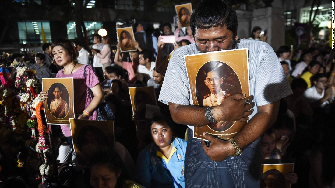 People react to news of the King's death outside Siriraj Hospital in Bangkok on Thursday.