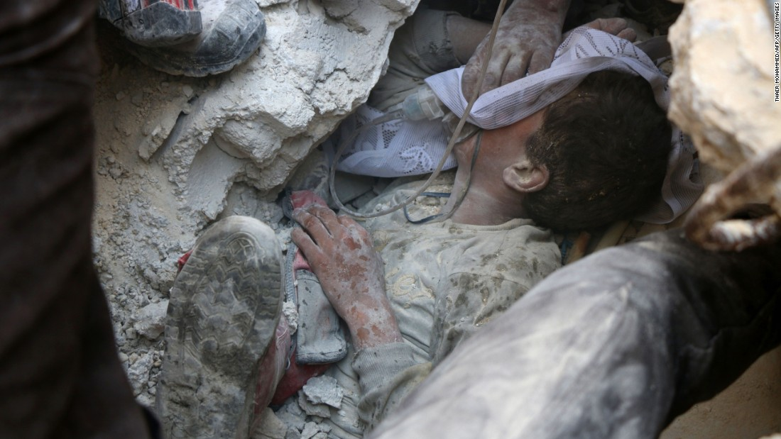 """Jameel Mustafa Habboush, a 13-year-old boy, receives oxygen as he is pulled alive from the rubble of a building in Aleppo, Syria, after airstrikes on Tuesday, October 11. <a href=""""http://www.cnn.com/2016/10/13/middleeast/syria-aleppo-airstrikes/index.html"""" target=""""_blank"""">Violence continues to rage</a> throughout various rebel-held neighborhoods in Aleppo."""