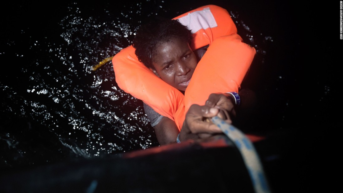 """A woman holds onto a rope during a migrant rescue operation near Libya's Mediterranean coast on Wednesday, October 12. Thousands of migrants have been making the dangerous journey across the Mediterranean, with many fleeing war-torn countries in Africa and the Middle East. <a href=""""http://www.cnn.com/2015/09/03/world/gallery/europes-refugee-crisis/index.html"""" target=""""_blank"""">Europe's migration crisis in 25 photos</a>"""