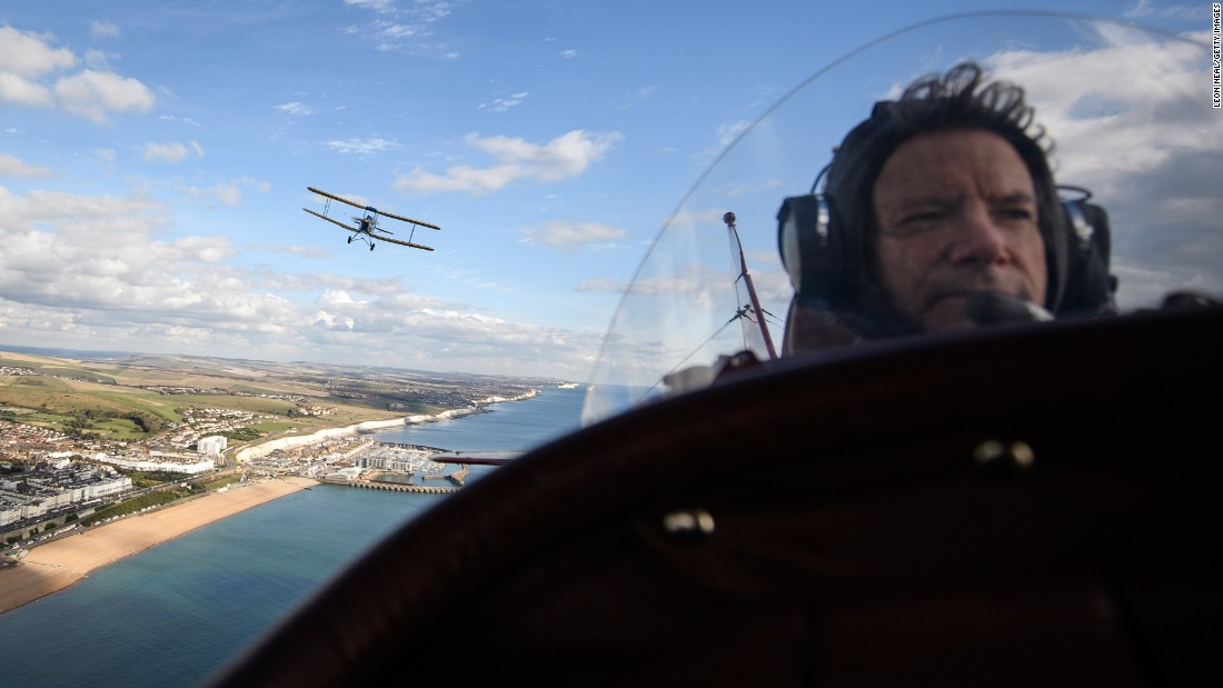 A Tiger Moth DH82A plane, flown by Ian Perry, is seen behind pilot Pedro Langdon during a promotional event for the upcoming Crete2Cape, a vintage air rally, in Brighton, England, on Monday, October 10. Pilots departed Crete, Greece, two days later, and will arrive in Cape Town, South Africa, in about five weeks.