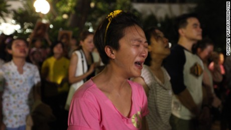 A Thai woman cries upon hearing that the nation's monarch had died.