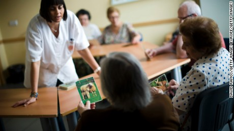 BARCELONA, SPAIN - AUGUST 02:  An elderly woman holds a picture of a sheep as she try to remenber the name of the animal during a memory activity at the Cuidem La Memoria elderly home, which specializes in Alzheimer patients on August 2, 2012 in Barcelona, Spain. The Government currently cannot pay the July allocations to old age homes and other social services as a result of liquidity issues. According to reports, Spain's most indebted region, Catalonia, is not be able to pay 400 millions euros in grants. Approximately one hundred thousand social workers will see their salary cut by 40% to 50% while relatives of elderly home residents have had to help pay the salaries and expenses.  (Photo by David Ramos/Getty Images)