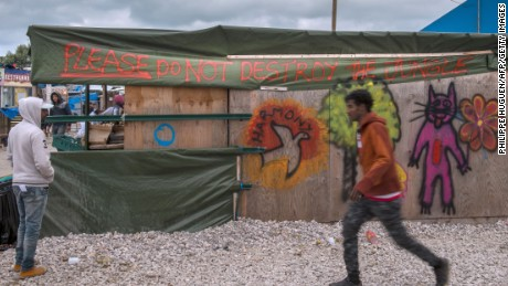 "A man walks past a shop spray painted with the words ""Please do not destroy the Jungle"" at the ""Jungle"" migrant camp in Calais on October 12, 2016. French authorities are preparing to raze the Calais ""Jungle"" camp and move thousands of migrants to shelters nationwide. / AFP / PHILIPPE HUGUEN        (Photo credit should read PHILIPPE HUGUEN/AFP/Getty Images)"