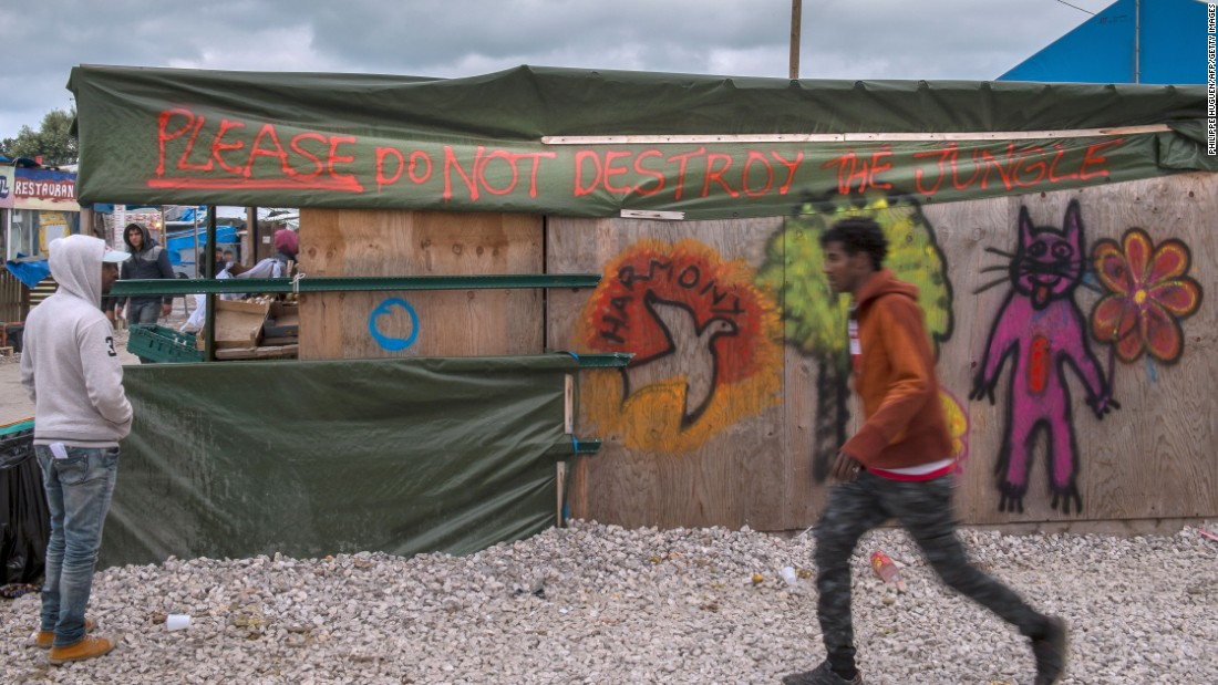 "A man walks past a shop spray-painted with the words ""Please do not destroy the Jungle"" at the migrant camp in Calais on October 12. French authorities are preparing to raze the Calais ""Jungle"" camp and move thousands of migrants to shelters nationwide."