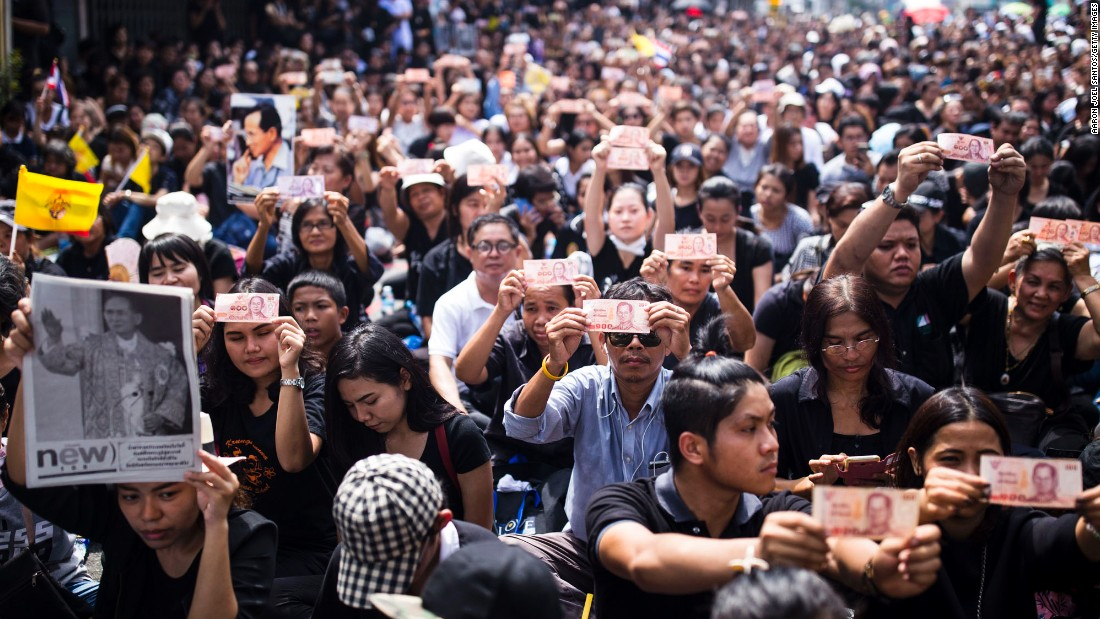 Thais gathering outside of Siriraj Hospital in Bangkok hold up baht notes with a portrait of Thailand's King Bhumibol Adulyadej on Friday, October 14, in Bangkok, Thailand, following news of his death the previous day.