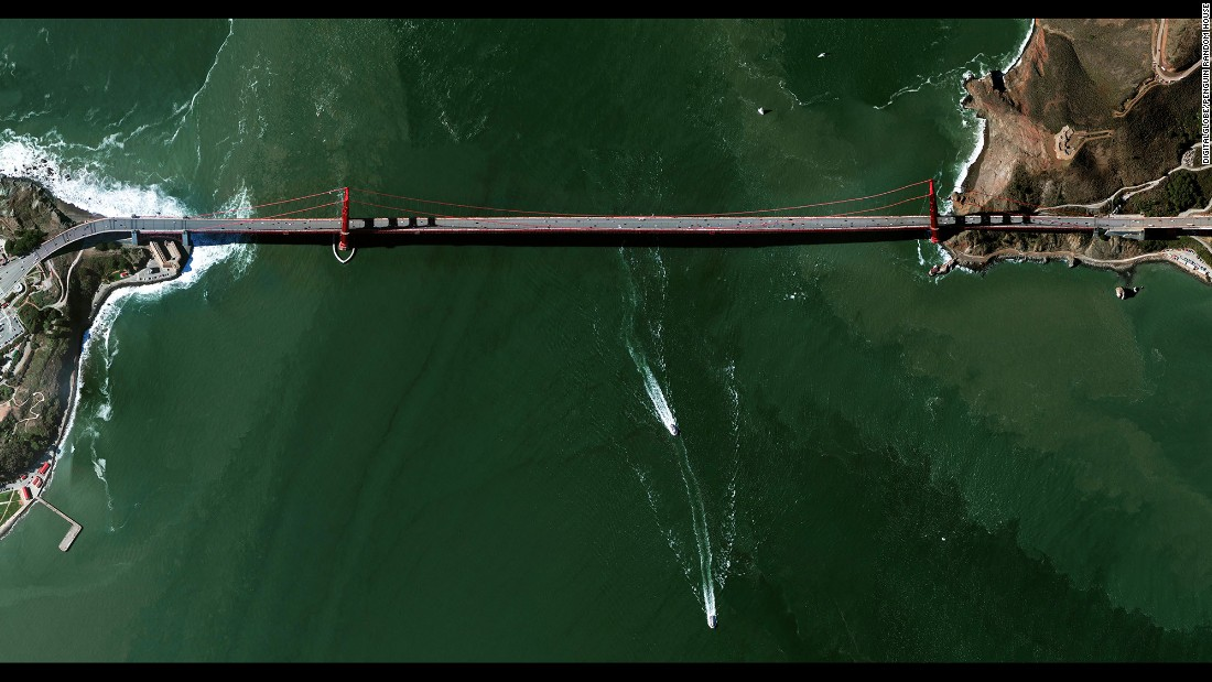 """The Golden Gate Bridge is a 1.7-mile-long suspension bridge in San Francisco. The bridge's signature color, known as """"international orange,"""" was selected to complement its natural surroundings and enhances its visibility in fog. Grant makes images like this one by stitching together various tiles of satellite imagery."""