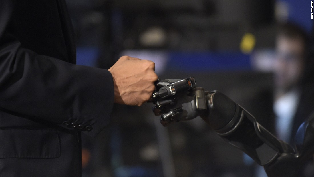 """President Barack Obama fist bumps with Nathan Copeland during the White House Frontiers Conference -- an event that explores the future of innovation around the globe -- in Pittsburgh, Pennsylvania, on Thursday, October 13. Copeland is paralyzed and uses a robotic arm controlled by a brain chip, which allows him to """"feel."""""""