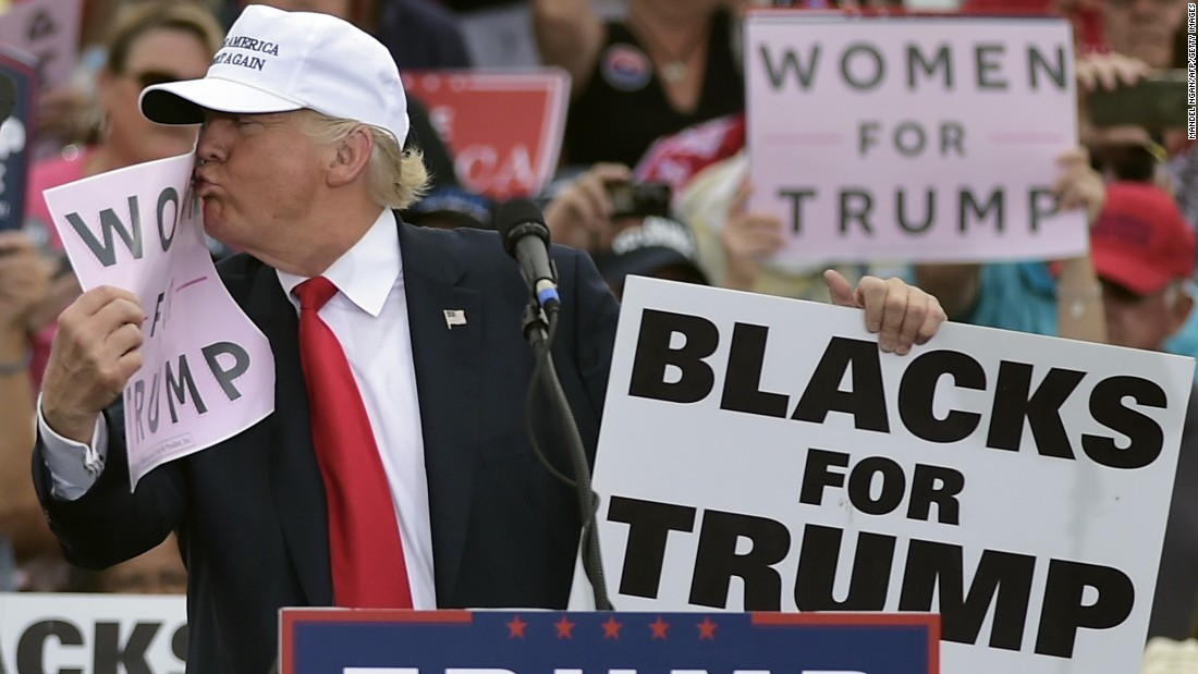 """Donald Trump,the Republican presidential nominee, kisses a """"Women for Trump"""" placard during a rally in Lakeland, Florida, on Wednesday, October 12."""