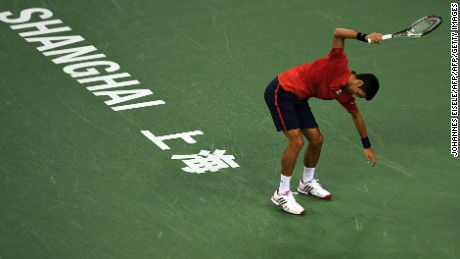 Djokovic smashes his racket after losing the first set.