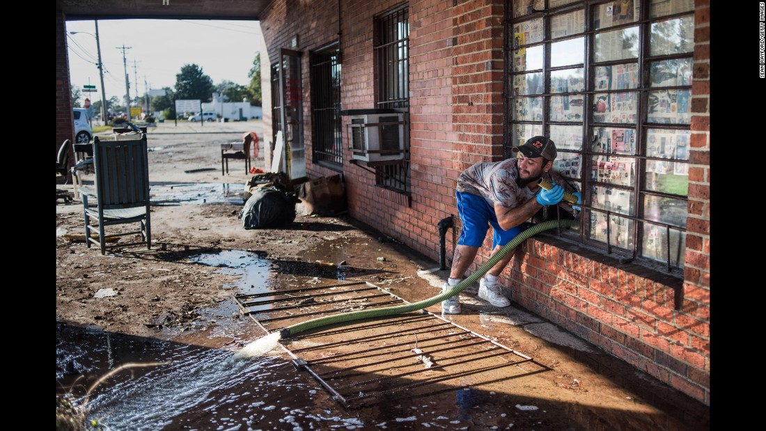 A man pumps floodwaters from the inside of a business on Saturday in Lumberton, the county seat of Robeson County, which was the area in North Carolina most affected by the storm.
